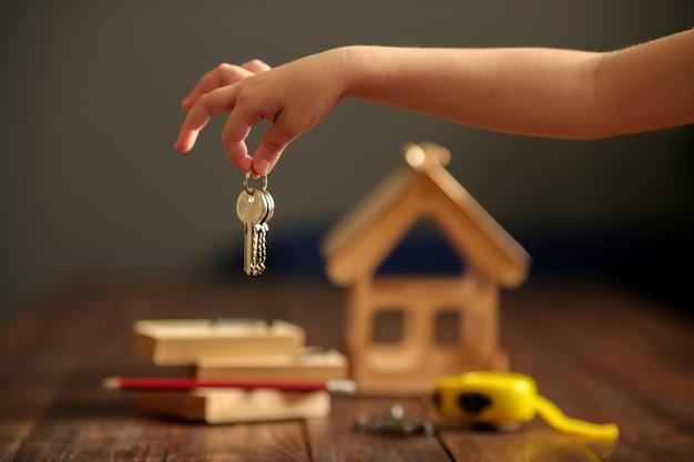Casa de madeira em uma superfície de madeira com tábuas e um molho de chaves com um chip