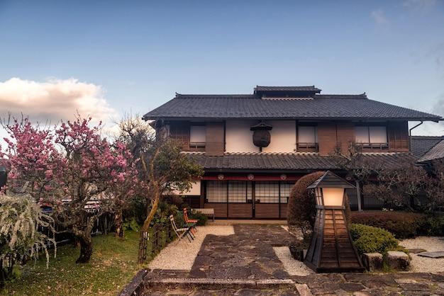 Casa de madeira japonesa tradicional com cerejeira sakura com céu azul em magome juku, vale kiso, nakatsugawa, gifu, japão. marco de viagens famoso no japão central.