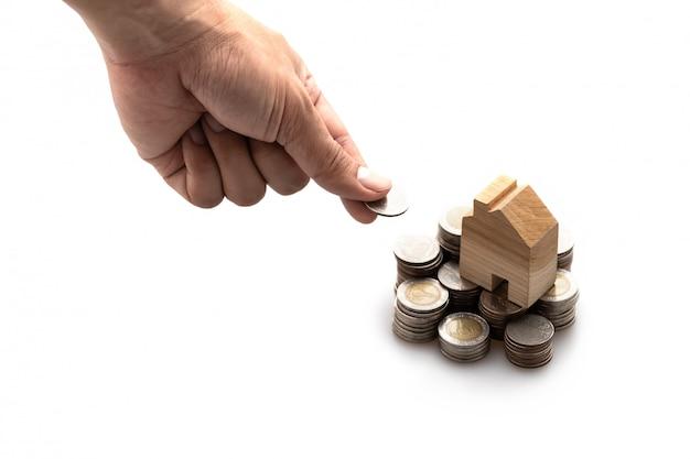 Casa de madeira modelada colocada em uma pilha de moedas e a mão esquerda do homem está colocando uma moeda