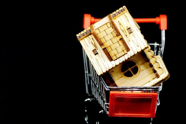Casa de madeira no carrinho de compras de brinquedo. imobiliário e conceito financeiro