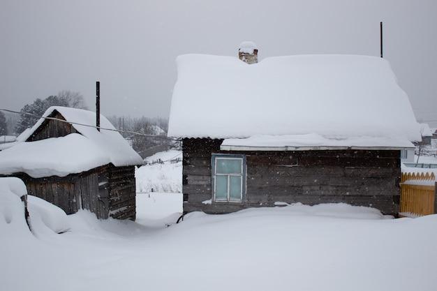 Casa de madeira no inverno na neve.