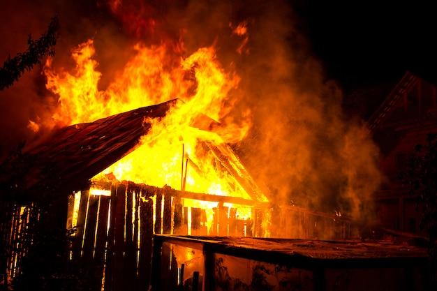 Casa de madeira ou celeiro queimando em chamas à noite.