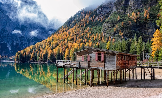 Casa de madeira pelo lago e montanha