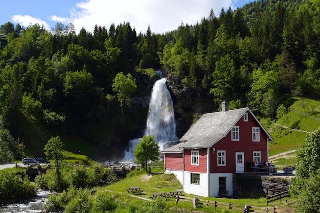 Casa de madeira tradicional norueguesa com cascata à distância