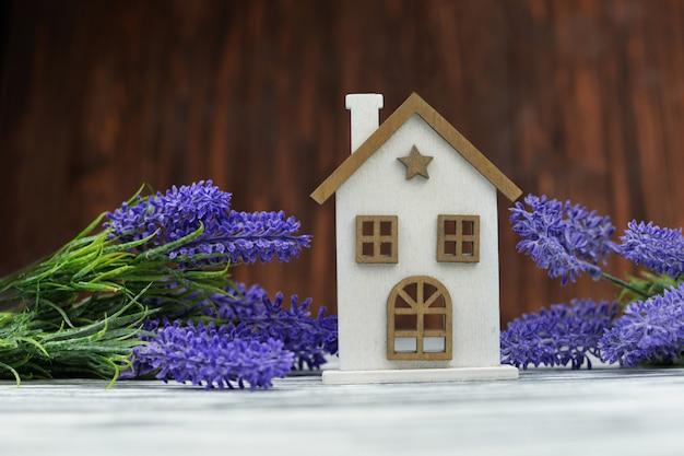 Casa de madeira um brinquedo branco acolhedor com flores