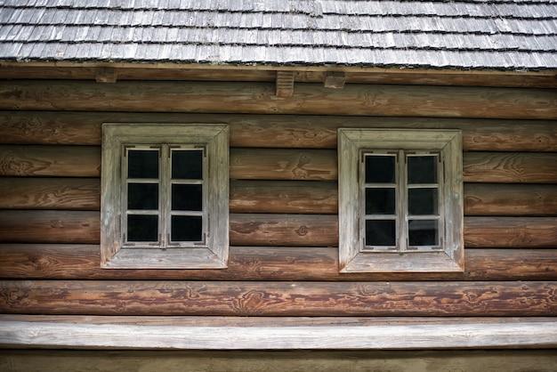 Casa de madeira velha com duas janelas. casa na zona rural. rústico.