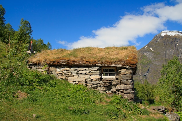 Casa de madeira velha com telhado de grama na noruega
