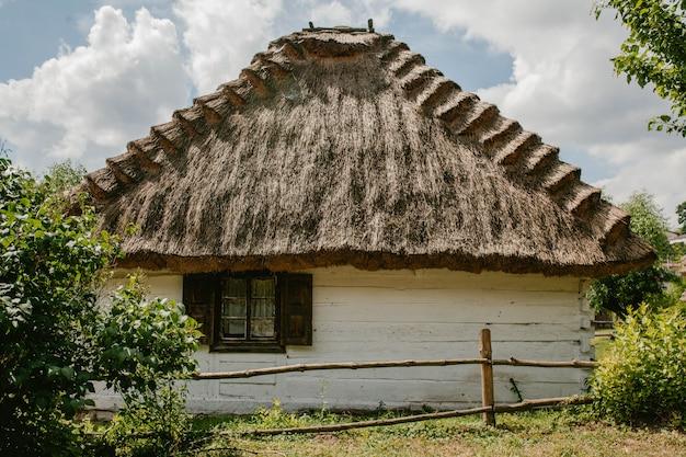 Casa de madeira velha com um telhado de palha e jardim