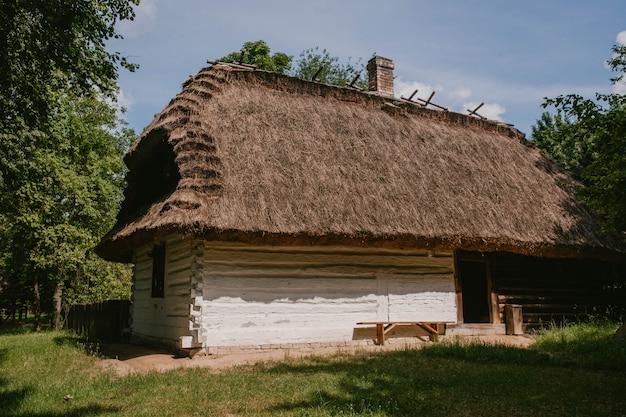 Casa de madeira velha com um telhado de palha