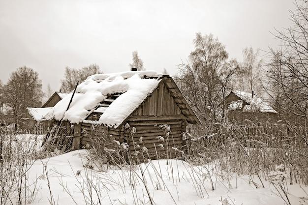 Casa de madeira velha entre a neve do inverno