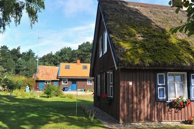 Casa de madeira velha velha, vermelha, no país europeu da lituânia, na cidade termal de nida, no espeto da curlândia.