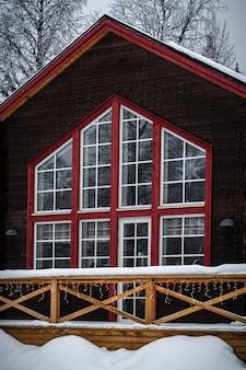 Casa de madeira vermelha e marrom com grandes janelas cobertas de neve em uma floresta cercada por árvores
