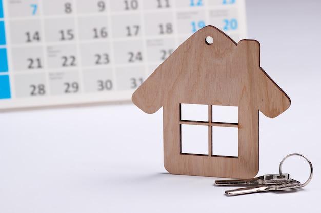 Casa de mini figura com calendário de mesa em fundo branco. conceito de pagamento de aluguel de habitação