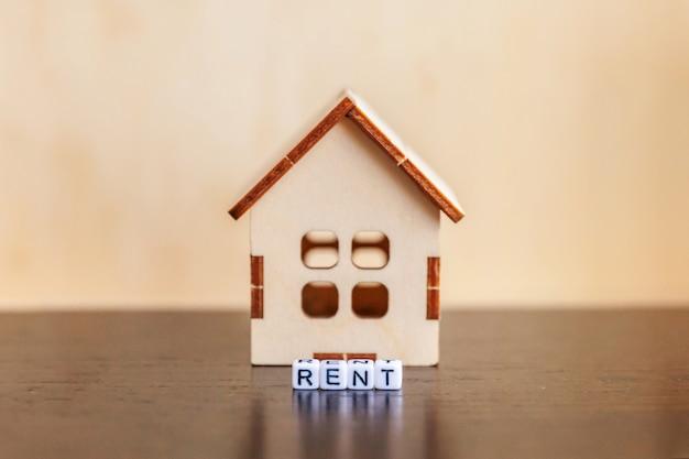 Casa de modelo de brinquedo em miniatura com inscrição aluga letras palavra sobre fundo de madeira. eco village, abstrato ambiental. conceito de aluguel de ecologia de lar doce hipoteca imobiliária imobiliário