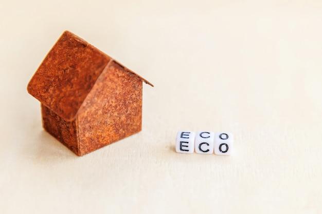 Casa de modelo de brinquedo em miniatura com inscrição eco letras palavra na superfície de madeira. eco village. ecologia zero resíduos responsabilidade social reciclar bio casa conceito