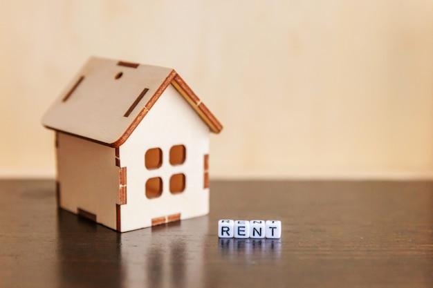 Casa de modelo de brinquedo em miniatura com inscrição palavra de letras de aluguel. eco village, abstrato ambiental. conceito de aluguel de ecologia de lar doce hipoteca imobiliária imobiliário