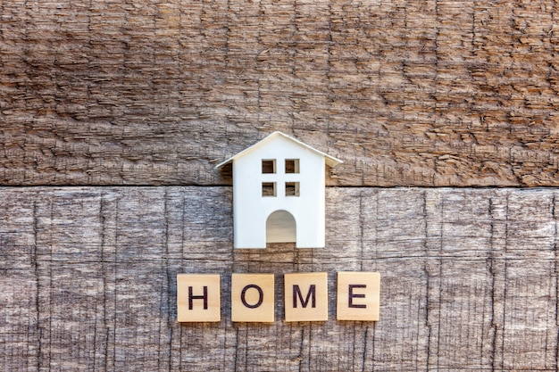 Casa de modelo de brinquedo em miniatura com palavra de letras casa inscrição em fundo de madeira