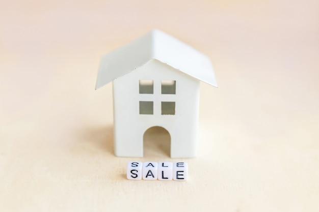 Casa de modelo de brinquedo em miniatura com palavra de letras de venda de inscrição no pano de fundo de madeira imóveis hipoteca propriedade seguro doce lar ecologia aluguel conceito