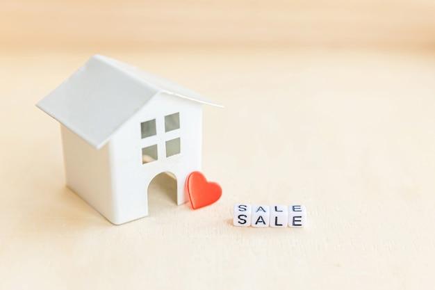 Casa de modelo de brinquedo em miniatura com palavra de letras de venda de inscrição no pano de fundo de madeira