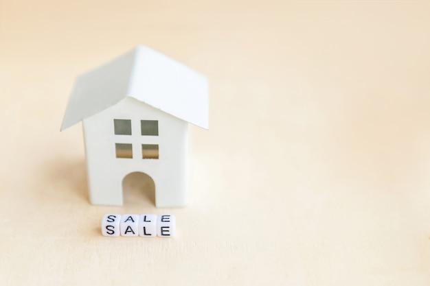 Casa de modelo em miniatura de brinquedo com inscrição venda letras palavra sobre fundo de madeira. eco village. conceito de aluguel de ecologia de lar doce hipoteca imobiliária imobiliário