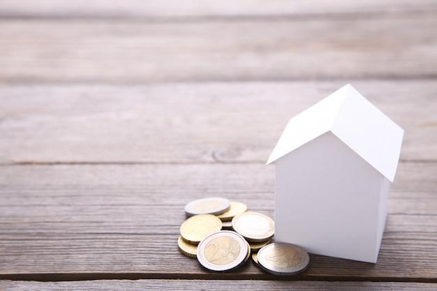 Casa de papel branco com moedas no fundo cinza