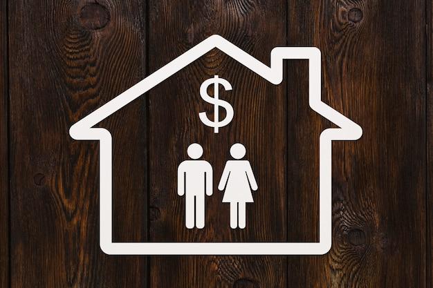 Casa de papel com homem, mulher e cifrão dentro de fundo de madeira.