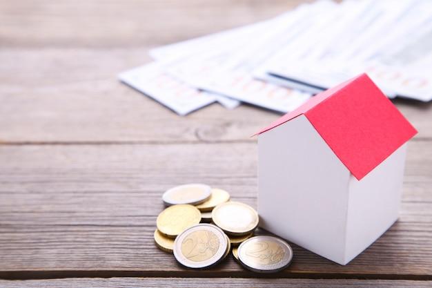 Casa de papel com telhado vermelho, com moedas