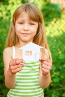 Casa de papel em mãos em um fundo de propriedade