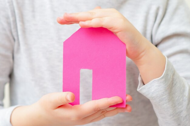 Casa de papel nas mãos de uma criança a sonhar com a casa. família e conceito de casa.