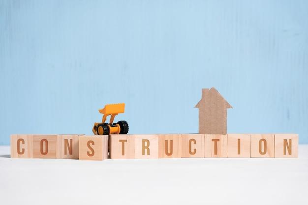 Casa de papelão abstrata ao lado de cubos de madeira com inscrições e equipamentos de construção.
