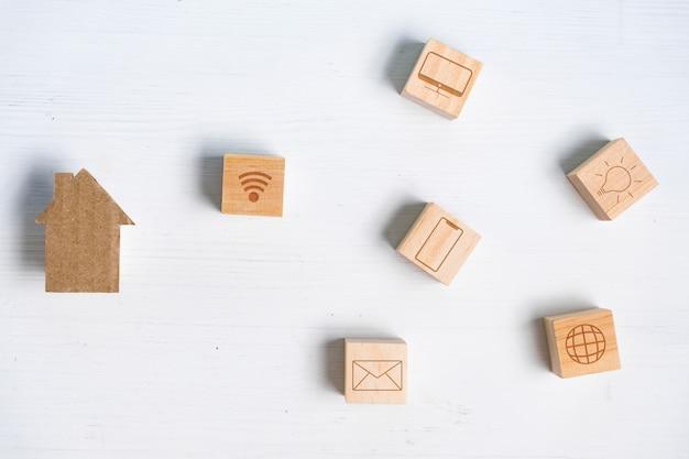 Casa de papelão abstrata ao lado de cubos representando uma casa inteligente. elementos da vida moderna e controle remoto.