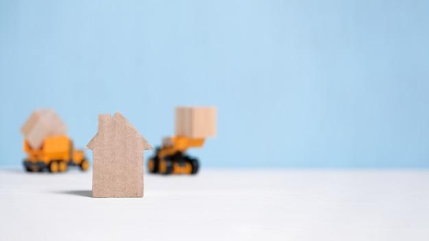 Casa de papelão abstrata ao lado de equipamentos de construção.