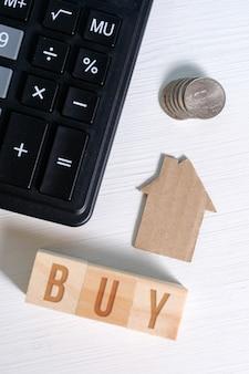Casa de papelão abstrata ao lado de uma calculadora e moedas, a palavra comprar. calcular o custo da habitação.