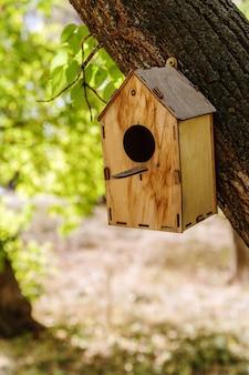Casa de passarinho de madeira presa a um tronco de árvore no parque da cidade outono na rússia na cidade de orenburg