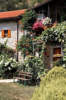 Casa de pedra com telhado de telhas rodeada de vegetação no jardim. fundo de verão