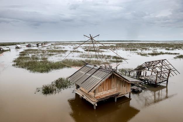 Casa de pescador em um pântano e armadilha para peixes de mergulho quadrado com chuva nublada e pouca luz