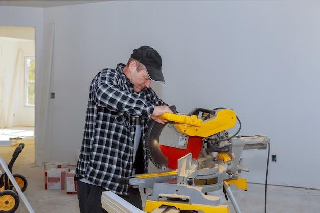 Casa de remodelação de construção, corte de acabamento de madeira com serra circular.