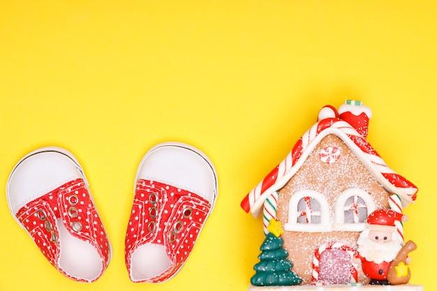Casa de reveillon com calçados infantis de cor vermelha com bolinhas brancas sobre fundo amarelo