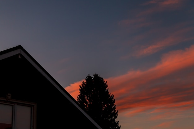 Casa de telhado e árvore no topo contra o fundo do sol à noite, céu azul com nuvens texturais