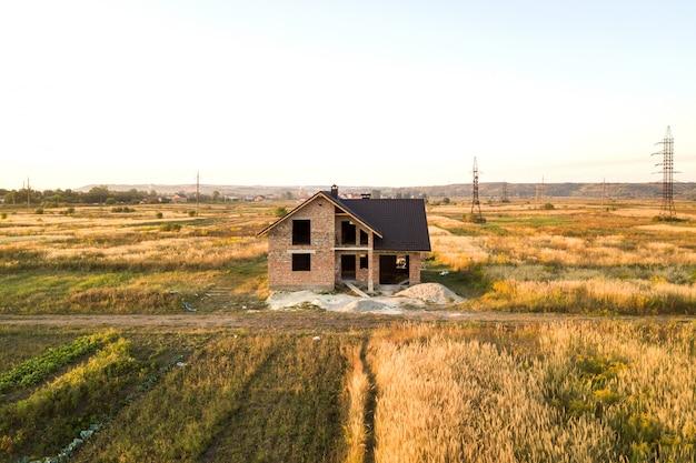 Casa de tijolo inacabado com telhado coberto com folhas de telha de metal em construção.