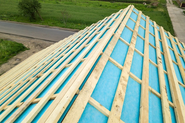 Casa de tijolos com estrutura de telhado de madeira em construção.