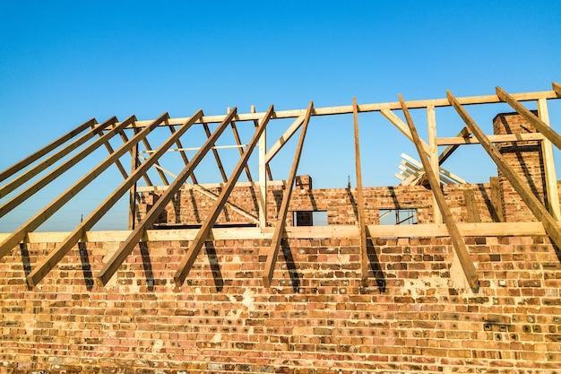 Casa de tijolos inacabada com estrutura de telhado de madeira em construção.