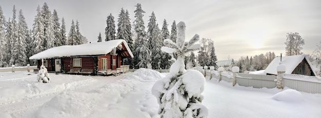 Casa de toras de madeira manchada de cor marrom escuro, com telhado coberto de neve na borda da floresta de abetos de inverno.
