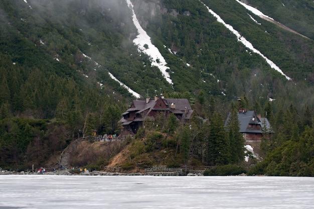 Casa de turista nas montanhas no lago de montanha congelada morsko oko