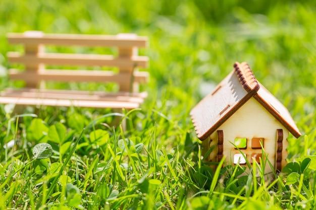 Casa decorativa de madeira pequena e banco pequeno na grama verde.