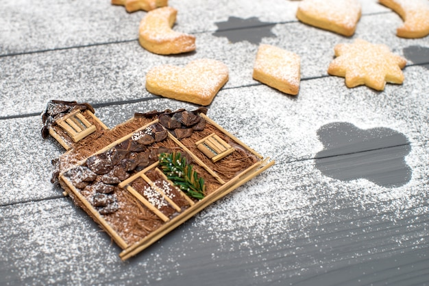 Casa decorativa de natal e biscoitos em forma de diferentes com açúcar em pó na mesa de madeira