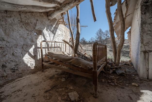 Casa destruída com velha cama de madeira dentro