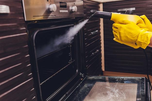 Casa do forno da limpeza de vapor que limpa o close-up da mão.