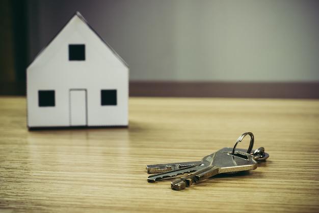 Casa do papel e chave no fundo de madeira