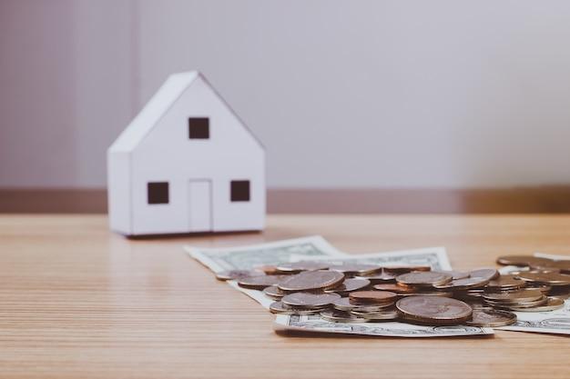 Casa do papel e dinheiro em fundo de madeira